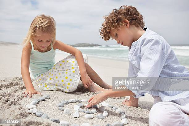 Siblings playing with pebbles on beach