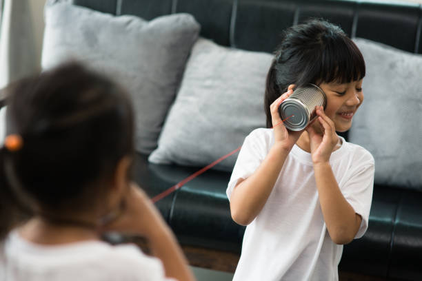 Siblings Playing With Tin Can Phones At Home