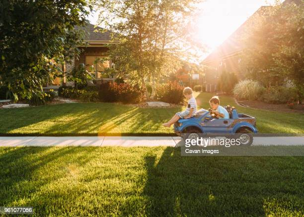 siblings playing with toy car on sidewalk at yard - happy family in car stock photos and pictures