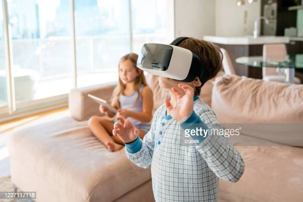 siblings playing with virtual reality glasses - izusek stock pictures, royalty-free photos & images