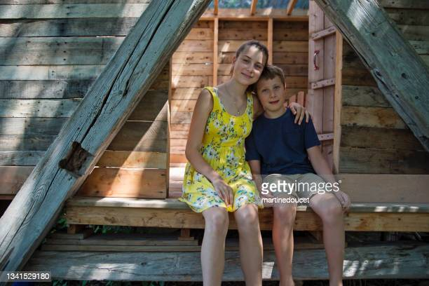 """siblings posing in treehouse in summer. - """"martine doucet"""" or martinedoucet stock pictures, royalty-free photos & images"""