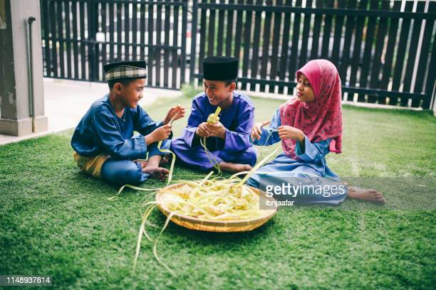 siblings preparing food in front of house - eid ul fitr stock pictures, royalty-free photos & images