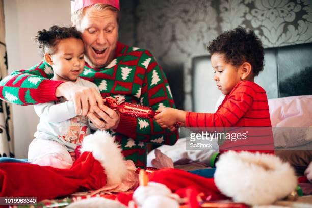 クリスマスの時に、父親とクリスマス クラッカーを引っ張って兄弟 - クリスマスクラッカー ストックフォトと画像