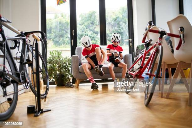 siblings put their shoes on getting ready for a bike ride - saltdean stock pictures, royalty-free photos & images