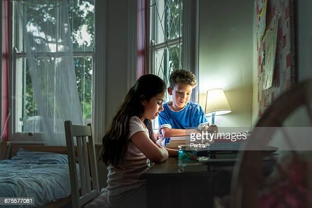 Siblings reading book by illuminated lamp at table
