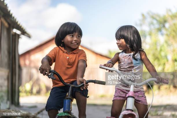 siblings riding a bicycle in a rural place - brazilian girls stock photos and pictures