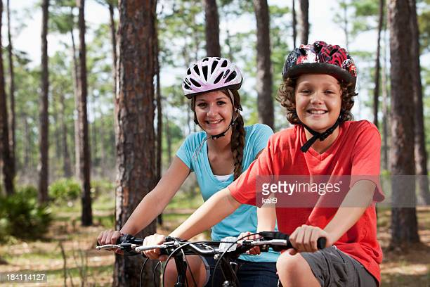siblings riding bicycles - lane sisters stock photos and pictures
