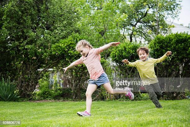 siblings (4-5), (6-7) running in backyard - juguetón fotografías e imágenes de stock