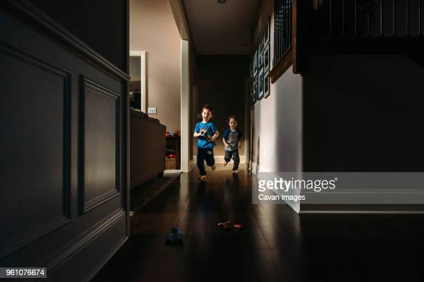 siblings running in hallway at home - brother stock pictures, royalty-free photos & images