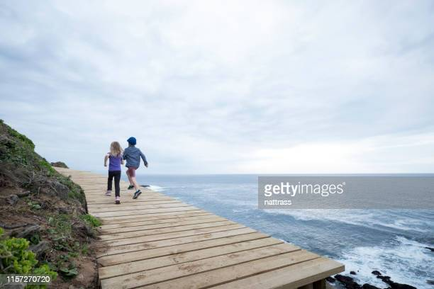 siblings running on boardwalk near sea - wide shot stock pictures, royalty-free photos & images