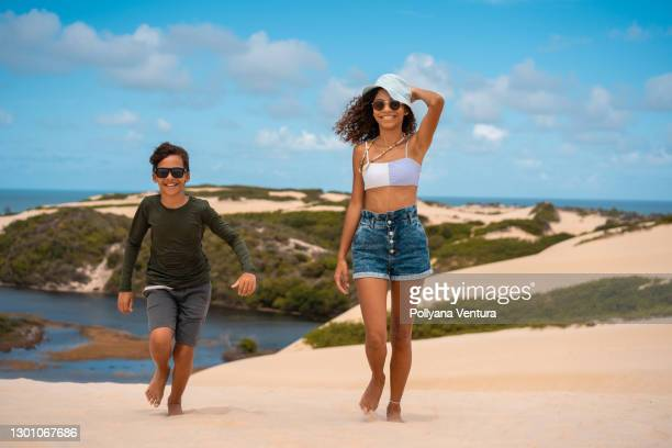 siblings running on the dunes in genipabu - natal brazil stock pictures, royalty-free photos & images