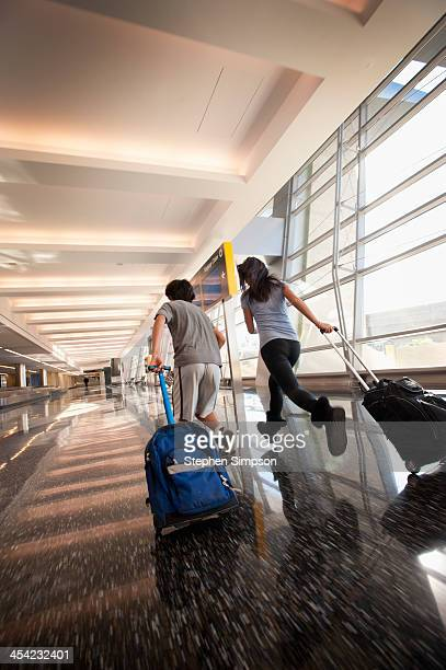 siblings rush through airport w/carry-on luggage