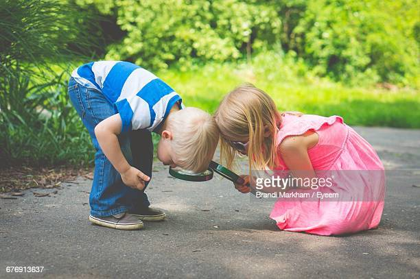 Siblings Searching With Magnifying Glass On Footpath At Park