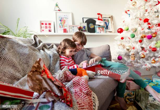 siblings sharing a digital tablet - happy new month stock photos and pictures