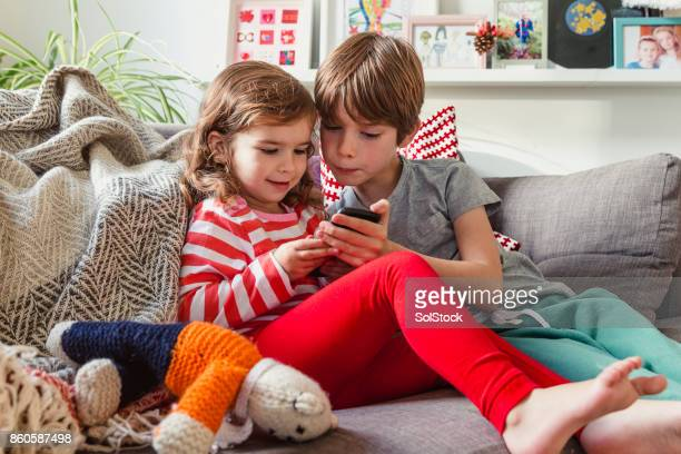 siblings sharing a mobile phone - happy new month stock photos and pictures