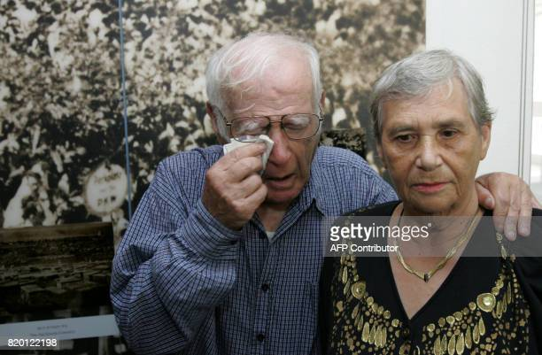Siblings Simon Glasberg of Ottawa Canada wipes his eyes as he stands with Hilda Shlick of Ashdod in southern Israel at Yad Vashem Holocaust Museum...