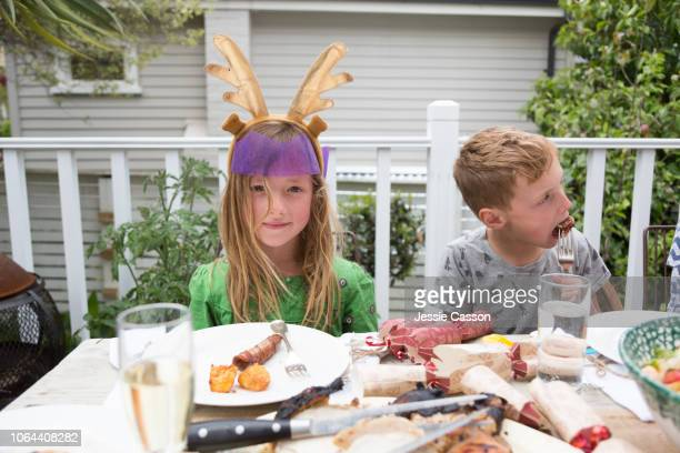 Siblings sit eating at the Christmas lunch table