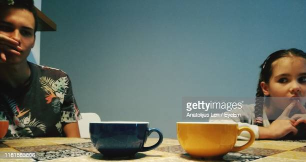 siblings sitting at table against wall - sister stock pictures, royalty-free photos & images
