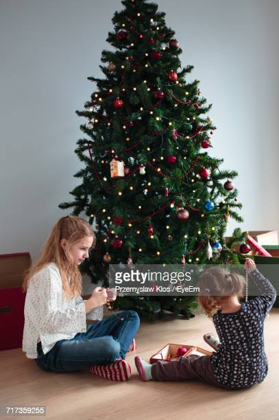 Siblings Sitting By Christmas Tree Against Wall At Home