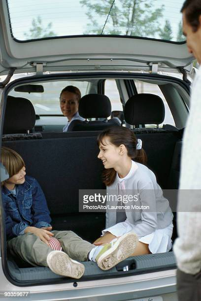 Siblings sitting in back of station wagon, parents watching