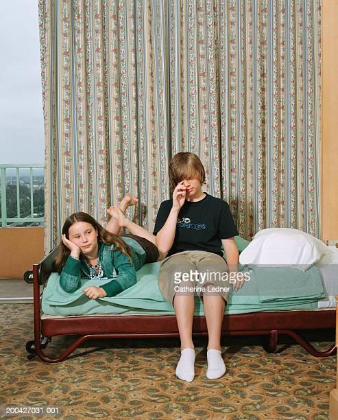 Siblings (10-14) sitting on bed