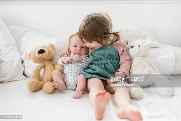 siblings (2-5 months, 2-3) sitting on bed with teddy bears - 2 5 months stock pictures, royalty-free photos & images