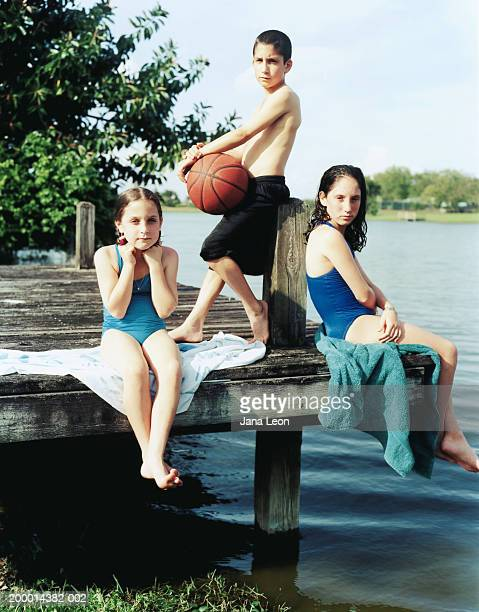 Siblings (6-12) sitting on dock, boy holding basketball