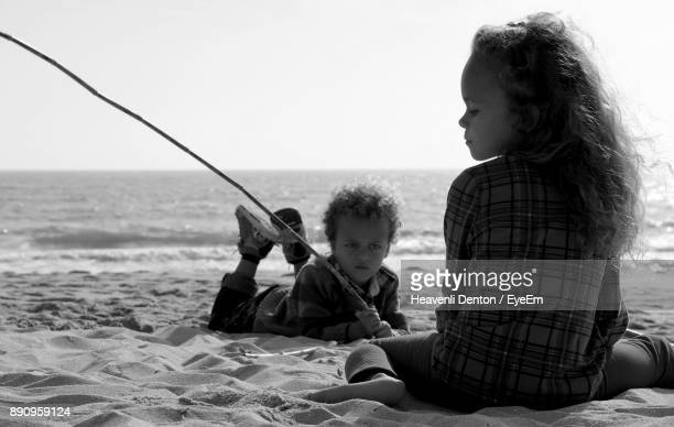 Siblings Sitting On Sand At Beach