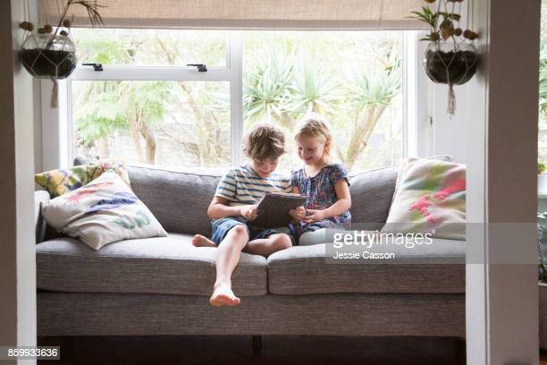 Siblings sitting on sofa looking at a device together