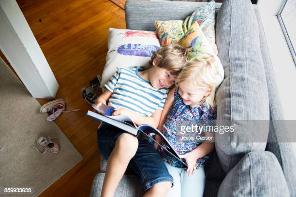 siblings sitting on sofa looking at book together - reading stock pictures, royalty-free photos & images