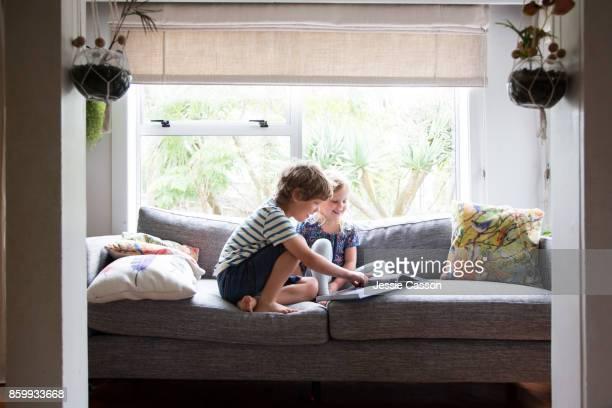 siblings sitting on sofa looking at book together - bruder stock-fotos und bilder