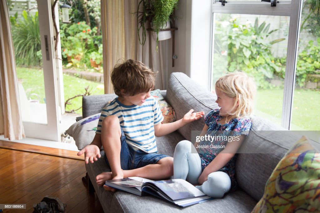 Siblings sitting on sofa looking at book together : Stock Photo