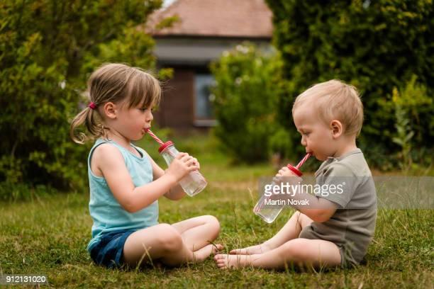 Siblings sitting together in backyard