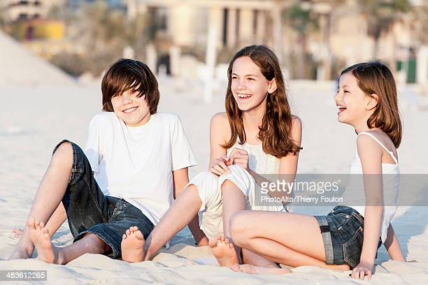 Siblings sitting together on sand at the beach