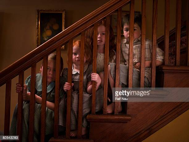 Siblings spying through staircase banister