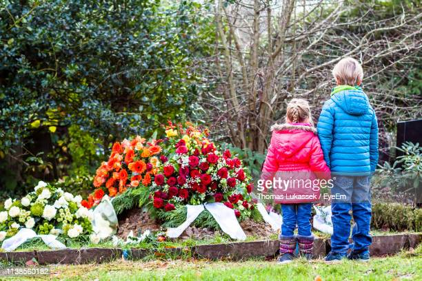 siblings standing against flowers in graveyard - cemetery stock pictures, royalty-free photos & images
