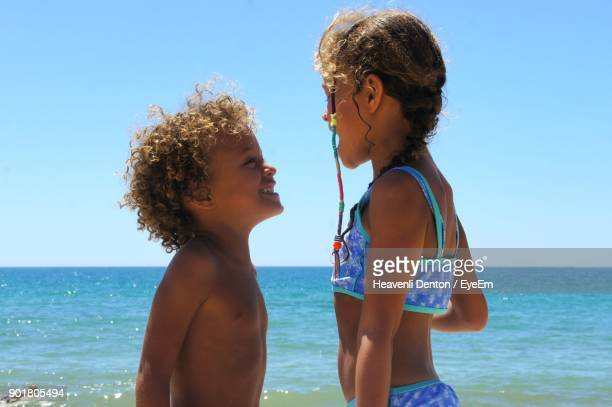 Siblings Standing Against Sea At Beach