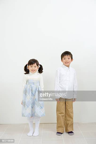 Siblings standing in a room