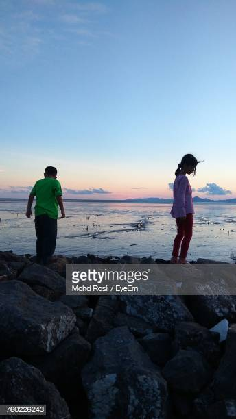 Siblings Standing On Rock At Beach Against Sky During Sunset