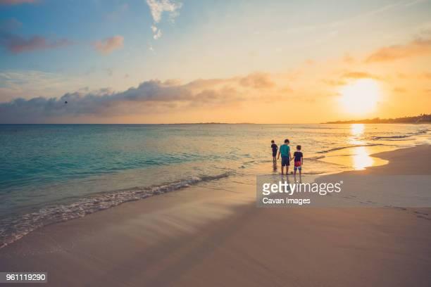 siblings standing on shore at beach against sky during sunset - paisajes de bahamas fotografías e imágenes de stock