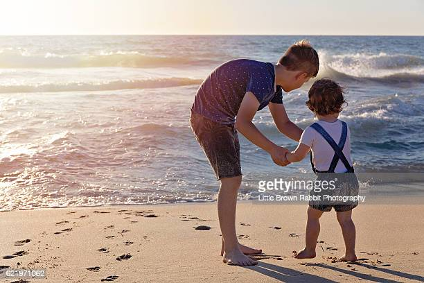 Siblings Standing on the Beach Shoreline at Sunset