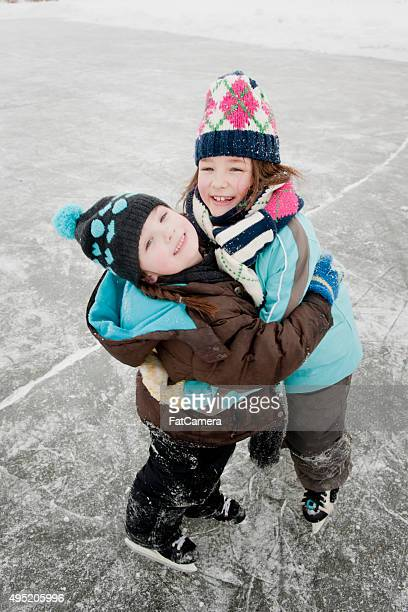 Siblings Standing on the Ice Wearing Their Skates