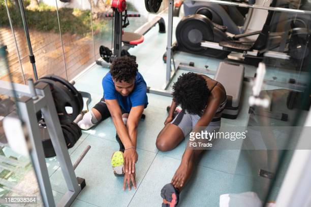 siblings stretching in gym - amputee woman stock pictures, royalty-free photos & images