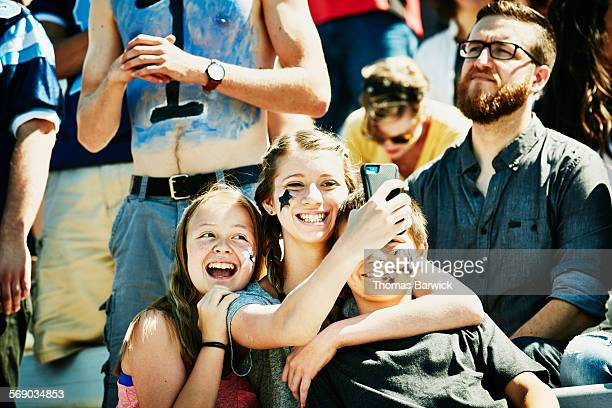 Siblings taking selfie during football game