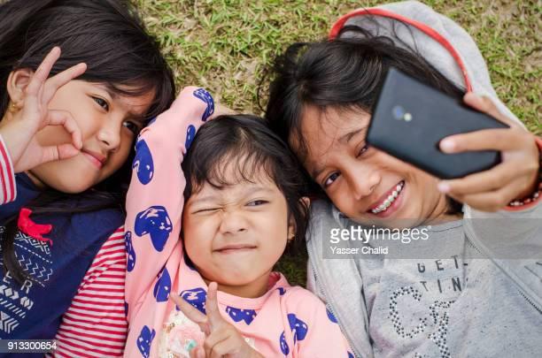Siblings Taking Selfie Lying On Grass