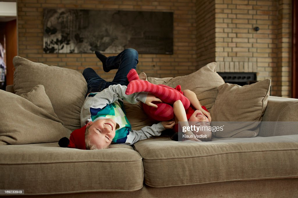 Siblings teasing each other in sofa : Stock Photo