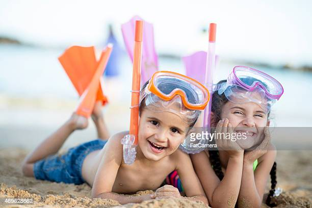 Siblings together on beach.