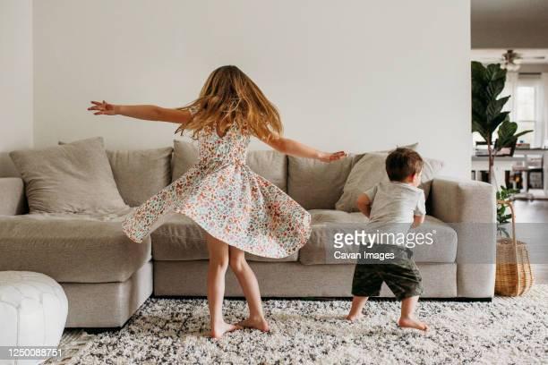 siblings twirling in living room - solo bambini foto e immagini stock