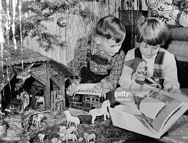 Siblings under the christmas tree with christman crib late fifties