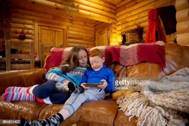 irmãos, usando um smartphone - ski holiday - fotografias e filmes do acervo